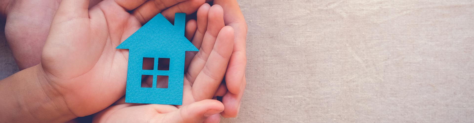 Child and adult holding blue paper image of a home