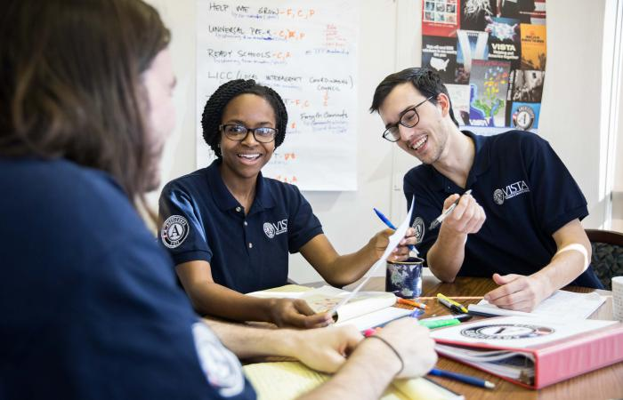 Two AmeriCorps VISTA members interact with a third person.