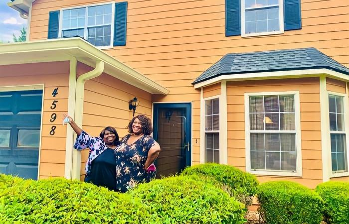 Anita James (left) and her daughter (right) smile brightly in front of their new home.