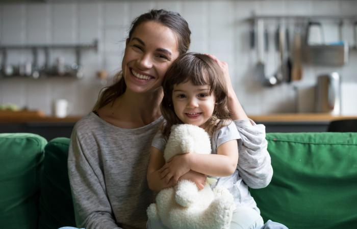 A mom smiles with her daughter.