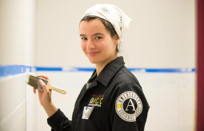 AmeriCorps volunteer paints a wall during a service project.
