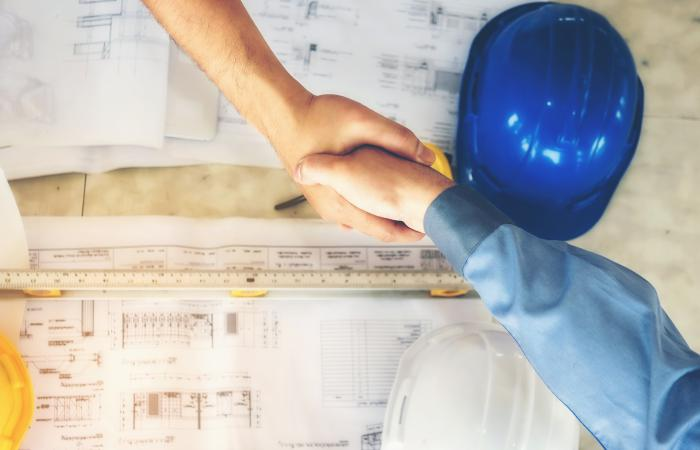 Two people shake hands over a hard had and blueprints.
