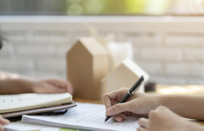 Woman putting signature on document loan contract, real estate purchase, success business contract deals with sale representative.